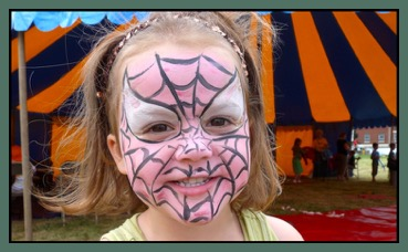 girl with facepaint, looking happy at an event with Circus Sensibles Big Top